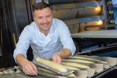 Υπερήφανο ψωμί baguette ψησίματος αρτοποιών στην κουζίνα στοκ εικόνες