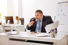 Υπερβολικός κουρασμένος εργαζόμενος που έχει ένα ανθυγειινό πρόχειρο φαγητό Στοκ Φωτογραφία