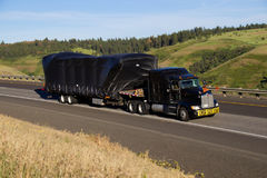 Υπεργέθες φορτίο/μαύρο ημι-φορτηγό Kenworth στοκ φωτογραφία
