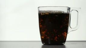 Υπερεμφανιζόμενα σιτάρια του μαύρου τσαγιού στο διαφανές φλυτζάνι φιλμ μικρού μήκους
