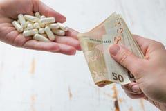 Υπερτιμώ? έννοια φαρμάκων - χέρια που ανταλλάσσουν τα χρήματα για τα φάρμακα Ιατρική ή σχετική με την ασφάλεια έννοια εγκλήματος Στοκ Εικόνες