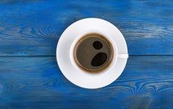 Υπερυψωμένη άποψη μιας πρόσφατα παρασκευασμένης κούπας του καφέ espresso στο μπλε αγροτικό ξύλινο υπόβαθρο με woodgrain τη σύστασ στοκ φωτογραφία
