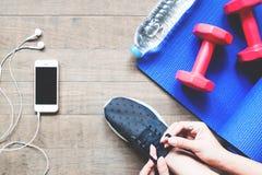 Υπερυψωμένη άποψη της γυναίκας στο μαύρο πάνινο παπούτσι με τον εξοπλισμό smartphone και αθλητισμού στο ξύλο Στοκ Εικόνες