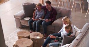 Υπερυψωμένη άποψη της οικογενειακής συνεδρίασης στην τηλεόραση προσοχής καναπέδων φιλμ μικρού μήκους
