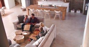 Υπερυψωμένη άποψη της οικογενειακής συνεδρίασης στον καναπέ που τρώει την πίτσα φιλμ μικρού μήκους