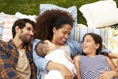 Υπερυψωμένη άποψη της οικογενειακής χαλάρωσης στην κουβέρτα στον κήπο από κοινού Στοκ Εικόνες