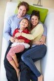 Υπερυψωμένη άποψη της οικογενειακής χαλάρωσης στον καναπέ στοκ εικόνα με δικαίωμα ελεύθερης χρήσης