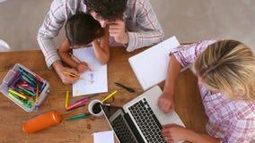 Υπερυψωμένη άποψη της οικογενειακών χρωματίζοντας εικόνας και της χρησιμοποίησης του lap-top απόθεμα βίντεο