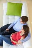 Υπερυψωμένη άποψη της χαλάρωσης ατόμων στον καναπέ με την έγκυο σύζυγο στοκ φωτογραφίες