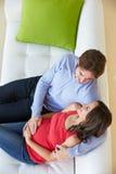 Υπερυψωμένη άποψη της χαλάρωσης ατόμων στον καναπέ με την έγκυο σύζυγο στοκ εικόνες