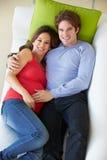 Υπερυψωμένη άποψη της χαλάρωσης ατόμων στον καναπέ με την έγκυο σύζυγο στοκ εικόνες με δικαίωμα ελεύθερης χρήσης