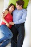 Υπερυψωμένη άποψη της χαλάρωσης ατόμων στον καναπέ με την έγκυο σύζυγο στοκ εικόνα