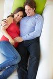 Υπερυψωμένη άποψη της χαλάρωσης ατόμων στον καναπέ με την έγκυο σύζυγο στοκ φωτογραφίες με δικαίωμα ελεύθερης χρήσης