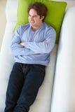Υπερυψωμένη άποψη της χαλάρωσης ατόμων στον καναπέ στοκ εικόνα