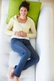 Υπερυψωμένη άποψη της χαλάρωσης γυναικών στον καναπέ στοκ φωτογραφία