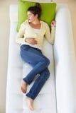 Υπερυψωμένη άποψη της χαλάρωσης γυναικών στον καναπέ στοκ εικόνα με δικαίωμα ελεύθερης χρήσης