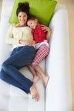 Υπερυψωμένη άποψη της χαλάρωσης μητέρων και κορών στον καναπέ στοκ φωτογραφία