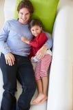 Υπερυψωμένη άποψη της χαλάρωσης πατέρων και κορών στον καναπέ στοκ φωτογραφίες