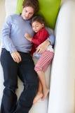 Υπερυψωμένη άποψη της χαλάρωσης πατέρων και κορών στον καναπέ στοκ φωτογραφία