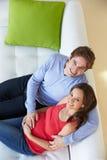 Υπερυψωμένη άποψη του ατόμου που προσέχει τη TV στον καναπέ με την έγκυο σύζυγο στοκ εικόνα