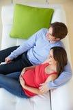 Υπερυψωμένη άποψη του ατόμου που προσέχει τη TV στον καναπέ με την έγκυο σύζυγο στοκ εικόνα με δικαίωμα ελεύθερης χρήσης