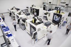 Υπερυψωμένη άποψη του εργαστηρίου εφαρμοσμένης μηχανικής με τους εργαζομένους που χρησιμοποιούν CNC Mac στοκ φωτογραφία με δικαίωμα ελεύθερης χρήσης
