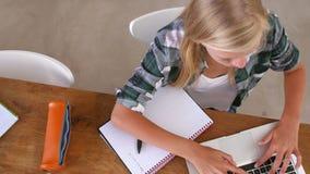 Υπερυψωμένη άποψη του κοριτσιού που κάνει την εργασία στον πίνακα στο lap-top απόθεμα βίντεο