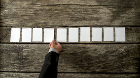 Υπερυψωμένη άποψη του πωλητή που τοποθετεί 10 κενές άσπρες κάρτες σε μια σειρά Στοκ φωτογραφία με δικαίωμα ελεύθερης χρήσης