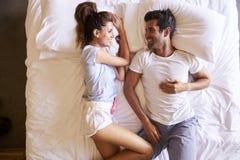Υπερυψωμένη άποψη του ρομαντικού ζεύγους που βρίσκεται στο κρεβάτι από κοινού Στοκ Εικόνες