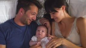 Υπερυψωμένη άποψη των γονέων που βρίσκεται στο αγκαλιάζοντας μωρό κρεβατιών απόθεμα βίντεο