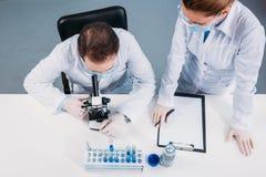 υπερυψωμένη άποψη των επιστημόνων στις ιατρικές μάσκες και των προστατευτικών διόπτρων που λειτουργούν στη επιστημονική έρευνα στοκ εικόνα με δικαίωμα ελεύθερης χρήσης