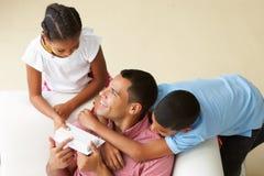 Υπερυψωμένη άποψη των παιδιών που δίνουν το δώρο πατέρων Στοκ Εικόνες