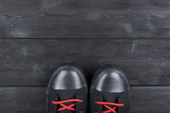 Υπερυψωμένη άποψη των παπουτσιών στο μαύρο ξύλινο πάτωμα Παπούτσια σε ένα ξύλινο υπόβαθρο Πάνινα παπούτσια σε ένα ξύλινο πάτωμα Α Στοκ εικόνα με δικαίωμα ελεύθερης χρήσης