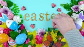Υπερυψωμένη επίδειξη άνοιξης Πάσχας των φρέσκων λουλουδιών στο μπλε ξύλο απόθεμα βίντεο
