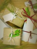 Υπερυψωμένη προοπτική μιας συλλογής των δώρων που τυλίγονται στα φυσικά άσπρα και καφετιά έγγραφα που δένονται με τη γιούτα και τ στοκ εικόνες