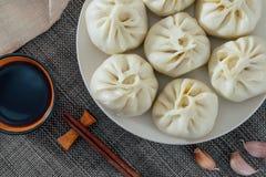 Υπερυψωμένη φωτογραφία ενός πιάτου των χειροποίητων βρασμένων στον ατμό κουλουριών και ενός πιάτου του ξιδιού από τη βόρεια Κίνα στοκ φωτογραφία