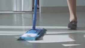 Υπερυψωμένος βλαστός της καθαρίζοντας κυρίας που χορεύει με μια σκούπα απόθεμα βίντεο