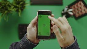 Υπερυψωμένος πυροβολισμός του ατόμου που χρησιμοποιεί το smartphone με την πράσινη οθόνη απόθεμα βίντεο