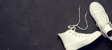 Υπερυψωμένος πυροβολισμός των άσπρων πάνινων παπουτσιών στο μαύρο υπόβαθρο Στοκ Εικόνα