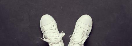 Υπερυψωμένος πυροβολισμός των άσπρων πάνινων παπουτσιών στο μαύρο υπόβαθρο Στοκ φωτογραφίες με δικαίωμα ελεύθερης χρήσης