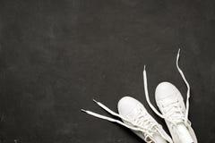 Υπερυψωμένος πυροβολισμός των άσπρων πάνινων παπουτσιών στο μαύρο υπόβαθρο Στοκ φωτογραφία με δικαίωμα ελεύθερης χρήσης