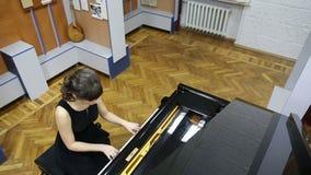 Υπερυψωμένος πυροβολισμός μιας ευτυχούς νέας γυναίκας που παίζει το μεγάλο πιάνο απόθεμα βίντεο