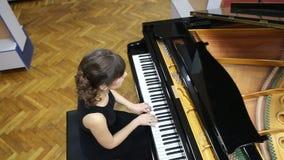 Υπερυψωμένος πυροβολισμός μιας ευτυχούς νέας γυναίκας που παίζει το μεγάλο πιάνο φιλμ μικρού μήκους