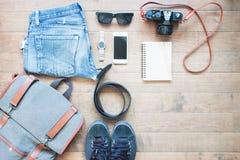 Υπερυψωμένος πυροβολισμός των προϊόντων πρώτης ανάγκης για τον ταξιδιώτη Εξάρτηση του ταξιδιώτη νεαρών άνδρων, κάμερα, κινητή συσ Στοκ Εικόνες