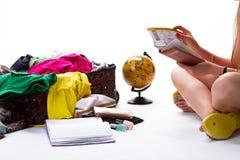 Υπερχειλισμένη βαλίτσα κοντά στο κορίτσι συνεδρίασης Στοκ Εικόνες