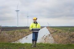 Υπεύθυνος για την ανάπτυξη προγράμματος σε ένα πράσινο τοπίο με τους ανεμόμυλους Στοκ φωτογραφία με δικαίωμα ελεύθερης χρήσης