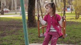 λυπημένο μικρό κορίτσι που ταλαντεύεται σε μια ταλάντευση απόθεμα βίντεο