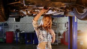 Υπηρεσία επισκευής αυτοκινήτων Ένας ανελκυστήρας αυτοκινήτων Η νέα γυναίκα στα μικρά σορτς περπατά κάτω από το αυτοκίνητο και καθ απόθεμα βίντεο