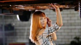 Υπηρεσία επισκευής αυτοκινήτων Ένας ανελκυστήρας αυτοκινήτων Νέες στάσεις γυναικών κάτω από το αυτοκίνητο και κοίταγμα στη κάμερα απόθεμα βίντεο
