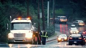 Υπηρεσία διακοπής αυτοκινήτων στον πολυάσχολο δρόμο στη βροχή απόθεμα βίντεο